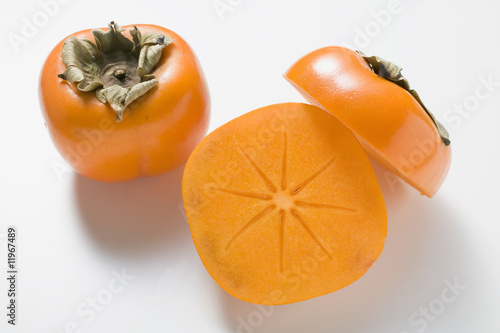 two persimmons, one halved