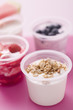 assorted yoghurts with cereals, berries and melon