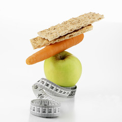 apple, carrot and crispbread with tape measure