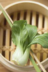 pak choi on chopsticks over bamboo steamer (overhead view)