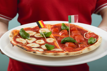 female footballer holding tomato & mozzarella pizza with flags