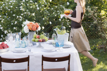 woman bringing iced tea to table laid in garden