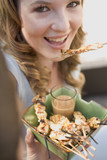 woman eating grilled satay with peanut dip