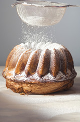 sprinkling gugelhupf with icing sugar