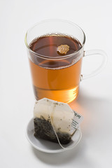 earl grey tea in glass cup, tea bag in foreground