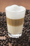 latte macchiato in glass on coffee beans