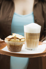 woman holding tray with latte macchiato and muffin