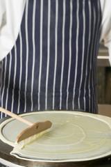 spreading pancake mixture on hotplate