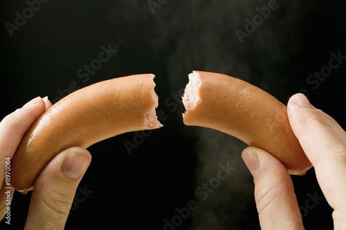 hands holding a halved frankfurter
