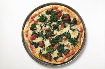 whole spinach, tomato and cheese pizza on plate
