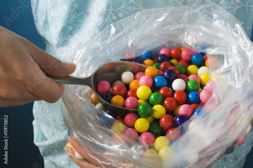 hand taking bubble gum balls out of plastic bag with scoop