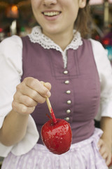 woman holding a toffee apple at oktoberfest