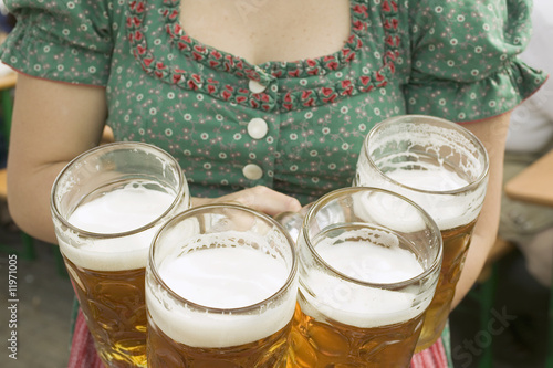 waitress in national dress serving four litres of beer (oktoberfest)