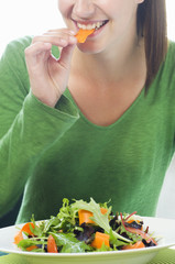 woman biting into slice of carrot, mixed salad leaves in front