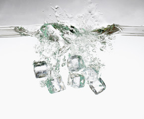 several ice cubes falling into water