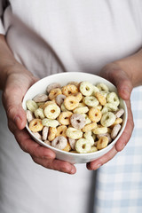 hands holding a bowl of multi-grain cereal loops