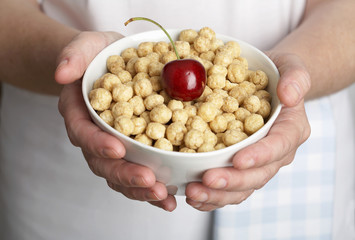 hands holding a bowl of toasted rice breakfast cereal with cherry
