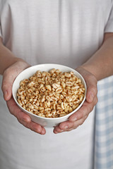 hands holding a bowl of puffed wheat breakfast cereal
