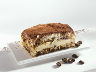 a piece of tiramisu and coffee beans