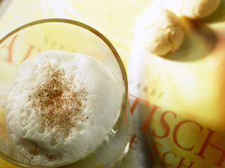 café latte with milk foam and almond biscuits on book