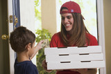 a boy paying a pizza delivery girl