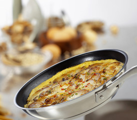 potato frittata with chili and chives in a frying pan