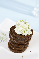 a pile of pumpernickel rounds with herb quark