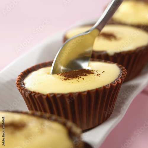 vanilla blancmange in chocolate case, a spoonful being taken