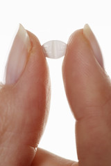 an allergy tablet between two fingers
