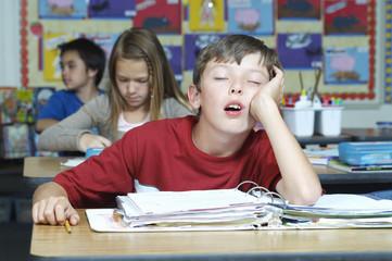 Three pupils in classroom, one of them sleeping