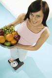 young woman standing on scales with bowl of fruit
