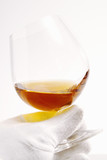 hand in white glove holding glass of cognac