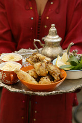 woman serving chicken with couscous, beans and lentils