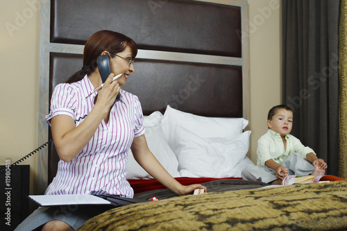 Business woman using phone with son on bed