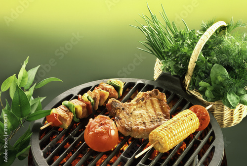 chop, kebab, sweetcorn and tomato on barbecue, fresh herbs