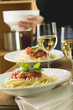 spaghetti bolognese and white wine for two on table