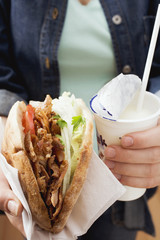 hands holding a döner kebab and drinking yoghurt