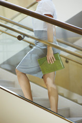 Business woman walking up stairs, mid-section