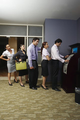 Business people queuing at vending machine