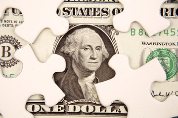 One dollar U.S. banknote and puzzle pieces