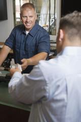 Man Paying for Repair Work