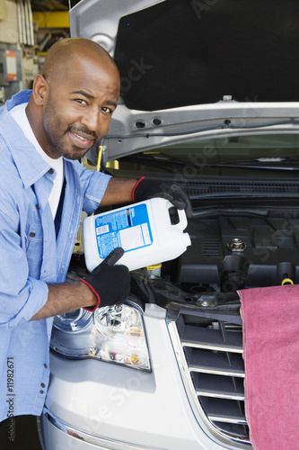 Auto Mechanic Adding Fluids to Minivan