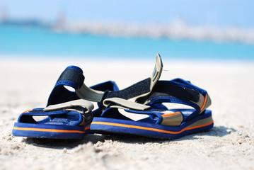 Pair of sandails at the seashore