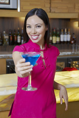 Woman Holding out a Blue Martini