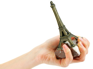 Woman's hand holding statuette of Eiffel Tower