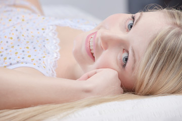 Cute blond girl on pillow in bedroom