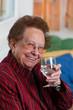 Seniorin trinkt Wasser aus einem Glas