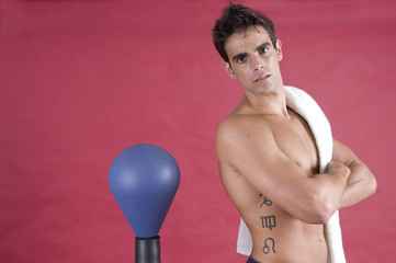 Young beauty man boxer fighting with punch bag