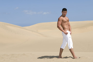 muscled man in the desert dunes with white troussers