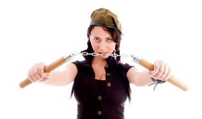 young woman wearing army cap and holding nunchaku